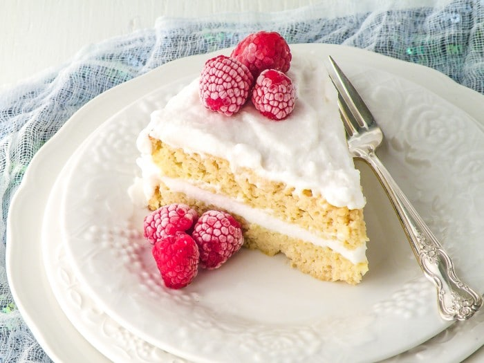Vanilla Coconut Flour Cake topped with raspberries on a white plate