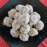 A pile of coconut date balls on a black plate on top of a red mat with white polka dots