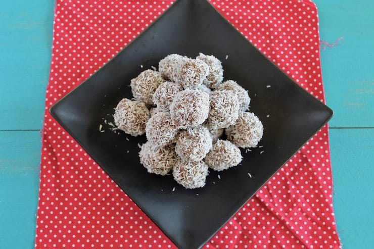 A pile of coconut date balls on a black plate on top of a red mat with white polka dots on a blue table