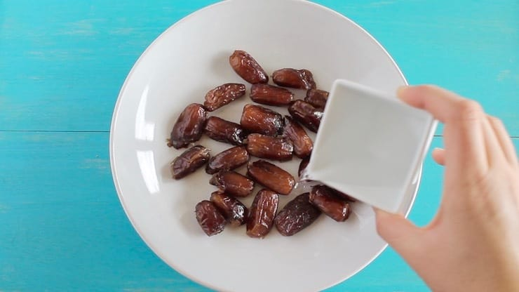 A hand pouring water over dates in a white bowl on a blue table