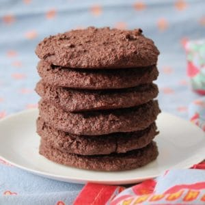 Six gluten free chocolate cookies stacked on top of each other on a white plate surrounded by blue table cloth with a red floral border