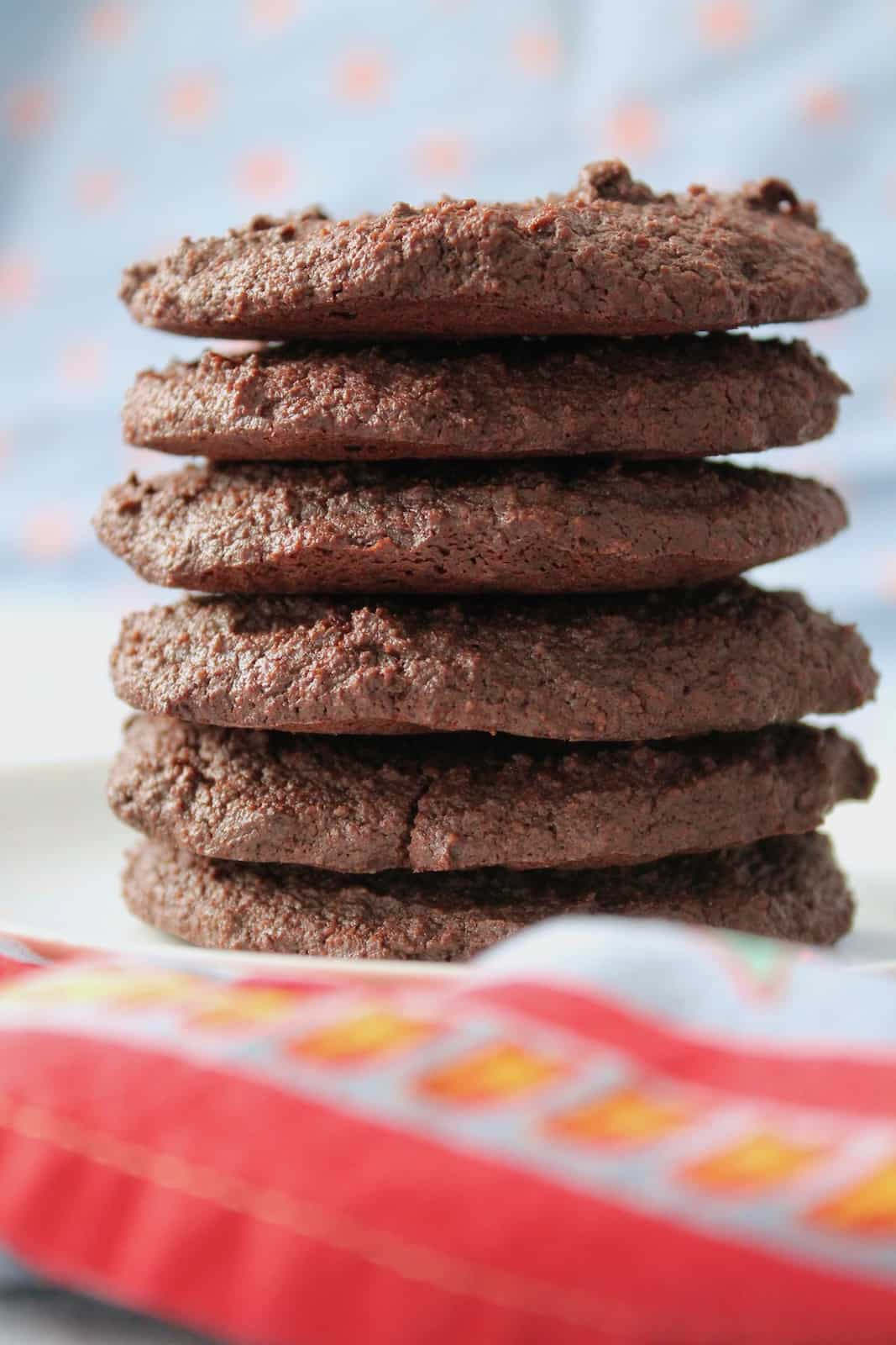 Close up shot of six gluten free chocolate cookies stacked on top of each other on a white plate surrounded by blue table cloth with a red floral border