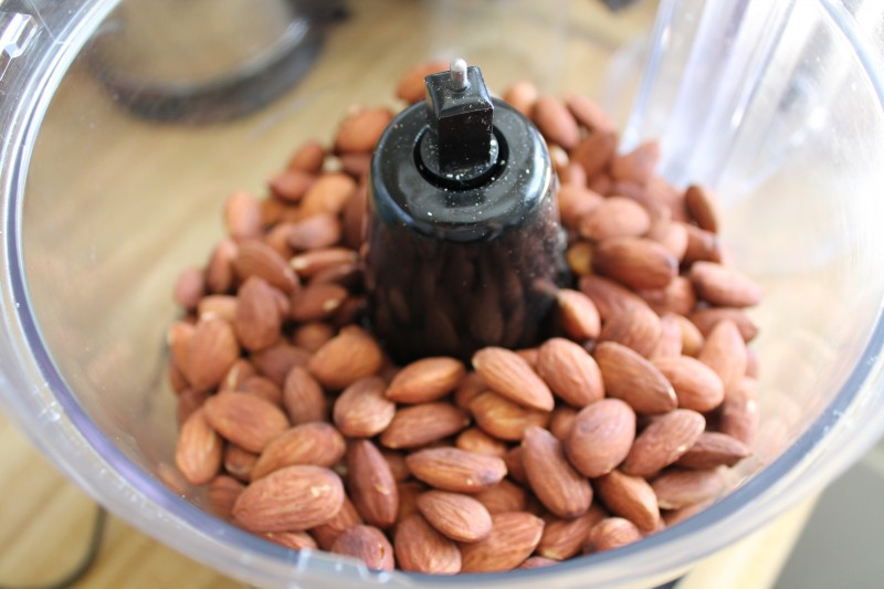 A process shot for how to make almond butter, almonds in a food processor