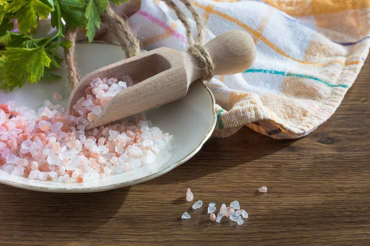 Pink himalayan rock salt on a plate with a wooden scoop on a wooden table
