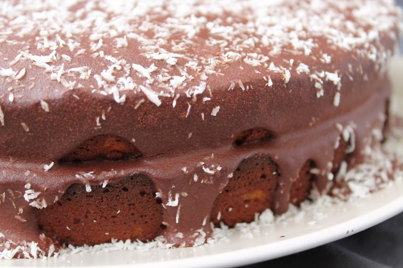A close up of vanilla cake with chocolate frosting dripping down the sides
