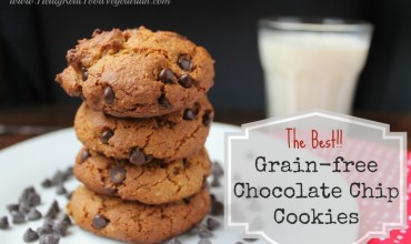 A pile of almond flour chocoalte chip cookies on a work surface with a glass of milk