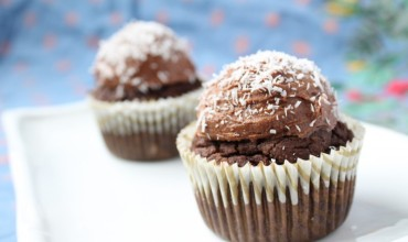 A close up of chocolate grain free cupcakes topped with coconut