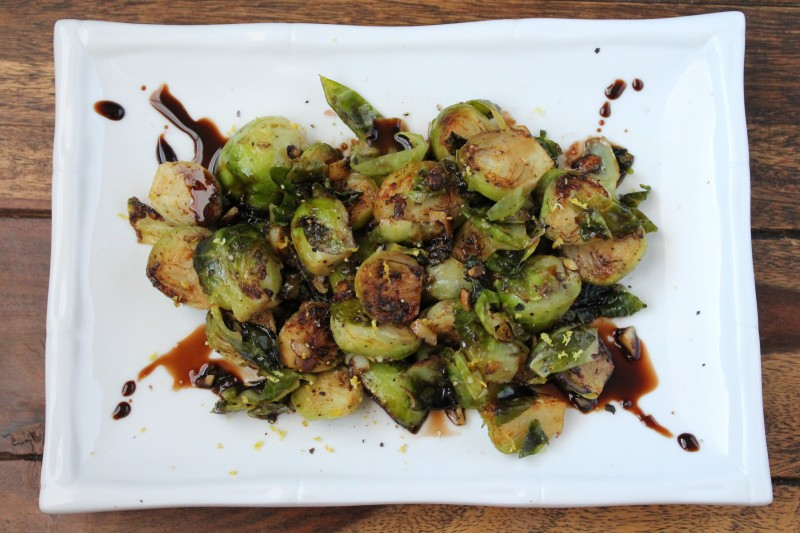 An overhead shot of lemon garlic brussels sprouts on a white plate with balsamic glaze