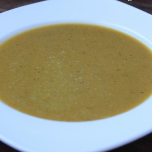 A close up of lentil butternut soup in a white bowl