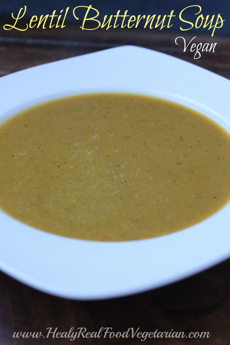 A close up of lentil butternut soup in a white bowl with a dark background