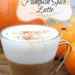 A close up of a vegan pumpkin spice latte in a glass mug sitting on a wooden surface