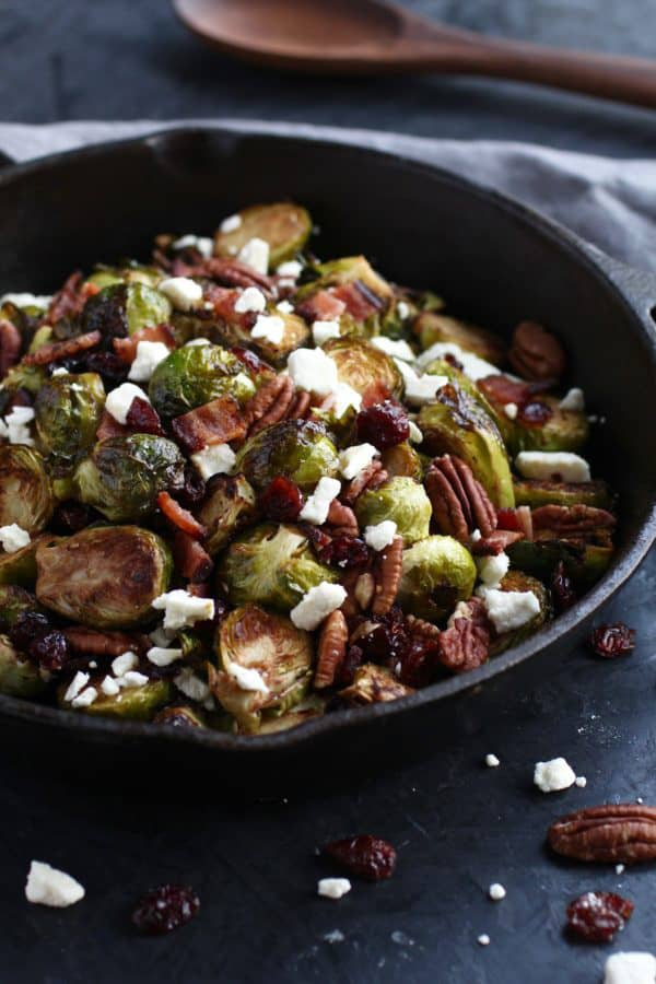 A close up of Brussels sprouts in a black bowl with feta, bacon and pecans