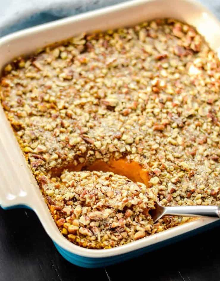 A close up of a sweet potato casserole with a spoonful getting scooped out