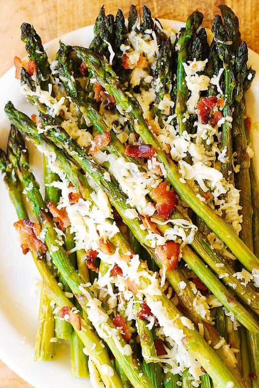 A close up of roasted asparagus with bacon and cheese