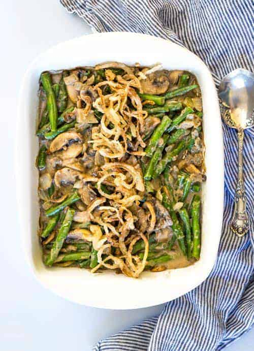 A green bean casserole in a white dish topped with crispy onions