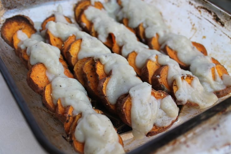Sweet potato rounds on a bkaing tray drizzled with cream sauce
