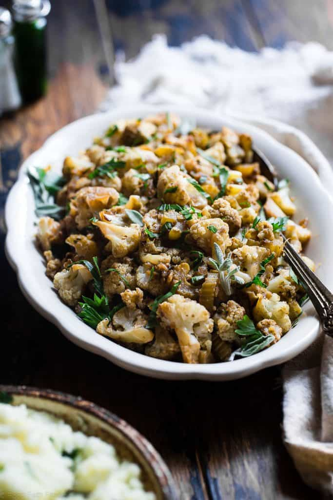 A close up of cauliflower stuffing on a plate with a serving spoon