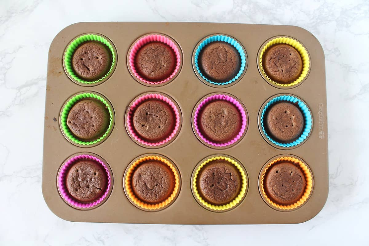 Overhead shot of muffin tin filled with baked chocolate muffins in muffin liners