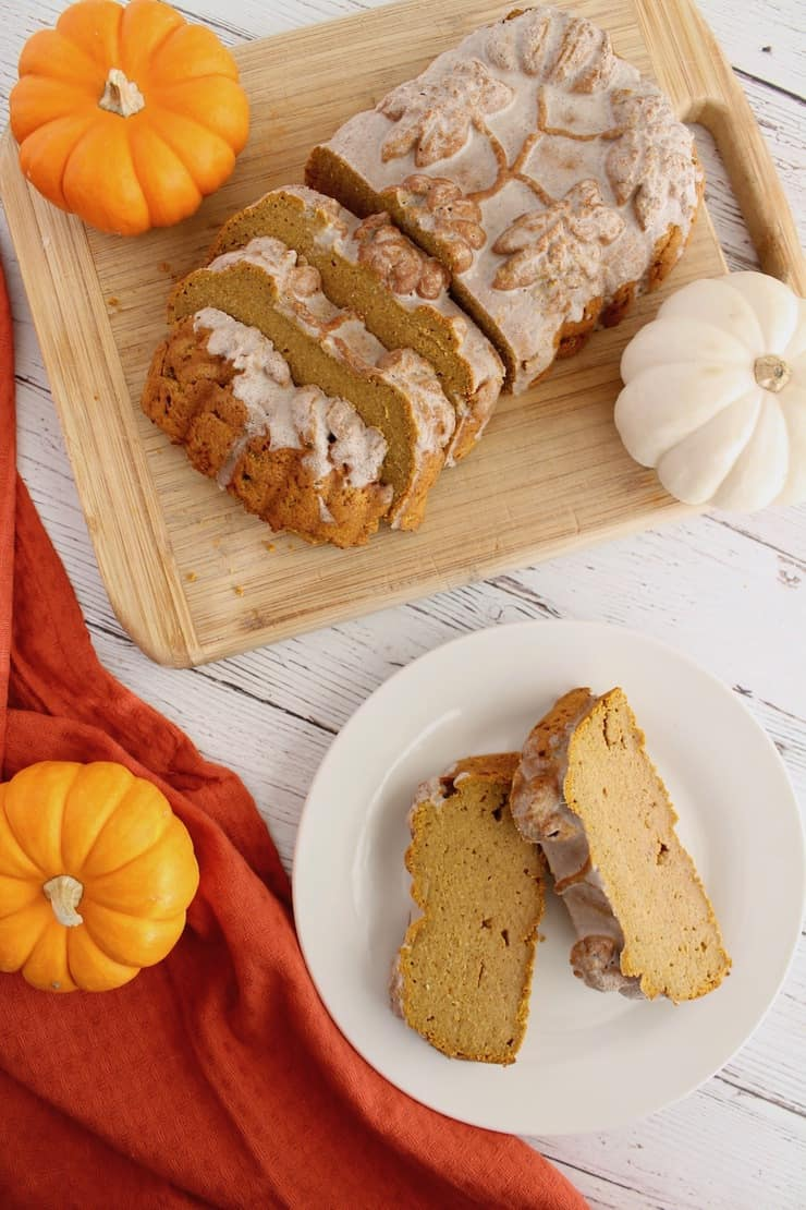 Overhead view of sliced load of healthy paleo pumpkin bread with white icing on top on wooden cutting board next to white plate with two slices of pumpkin bread on it