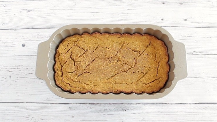 Baked paleo pumpkin batter in loaf pan on white wooden surface