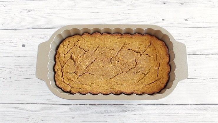 Baked paleo pumpkin batter in loaf pan on white wooden surface