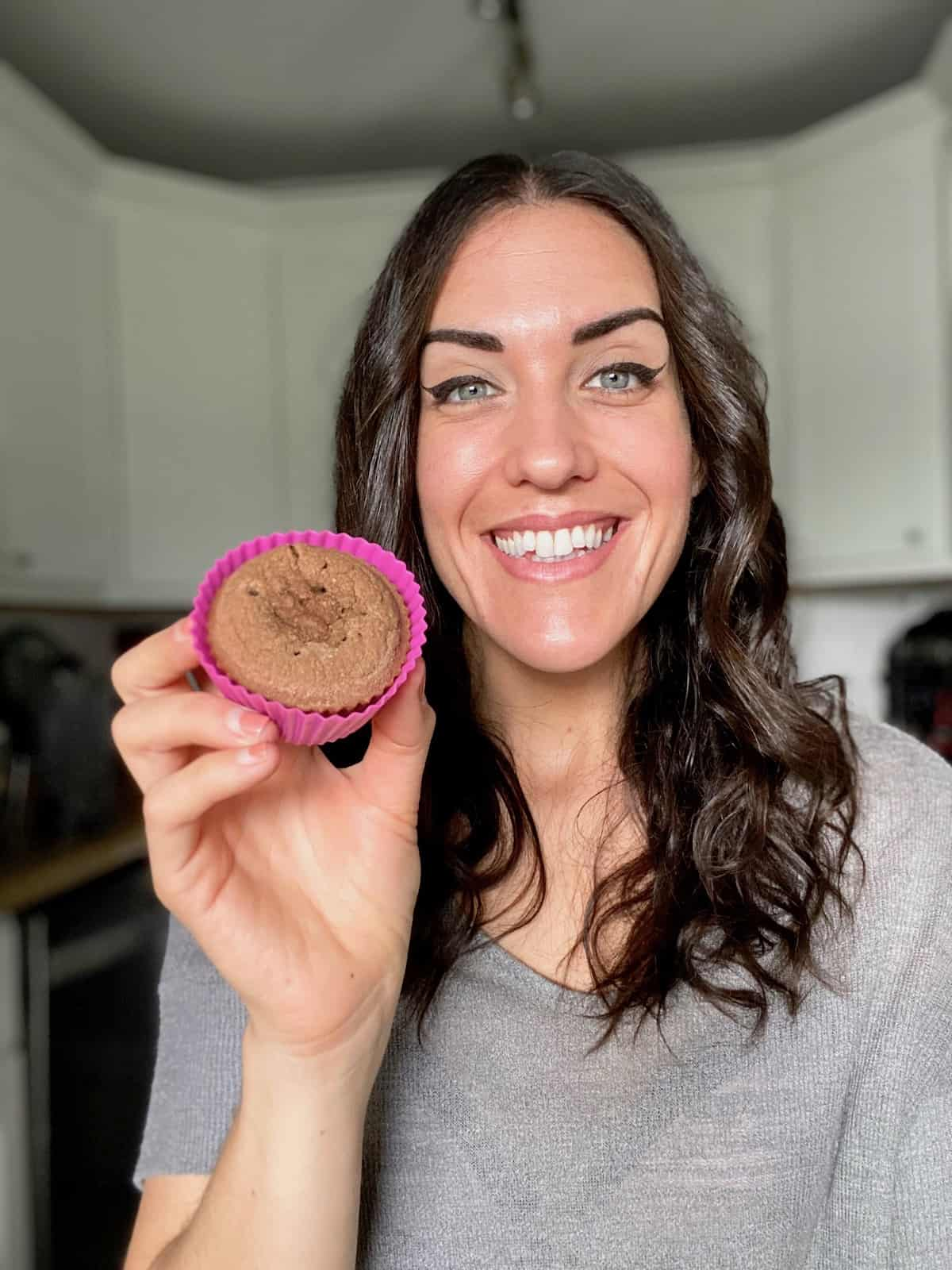 Smiling dark haired woman in grey shirt holding up a keto chocolate muffin in a pink muffin liner