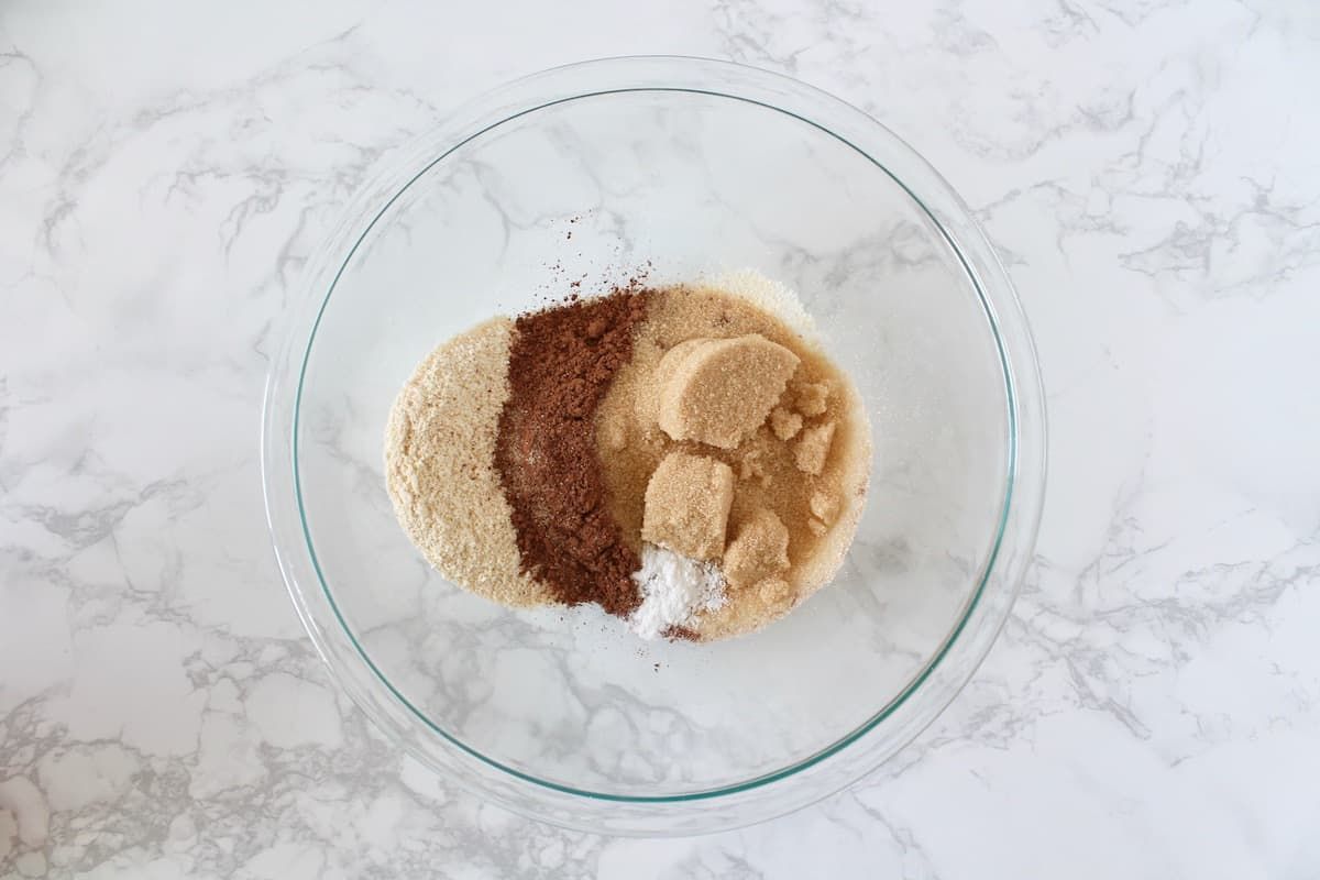 Overhead shot of clear mixing bowl with various dry baking ingredients in it on a white marble surface