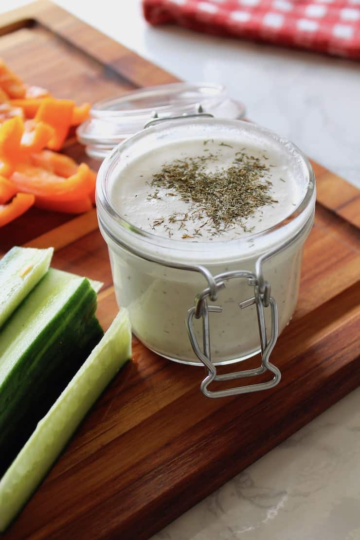 close up of paleo ranch dressing in a jar on a wooden cutting board with sliced vegetables next to it