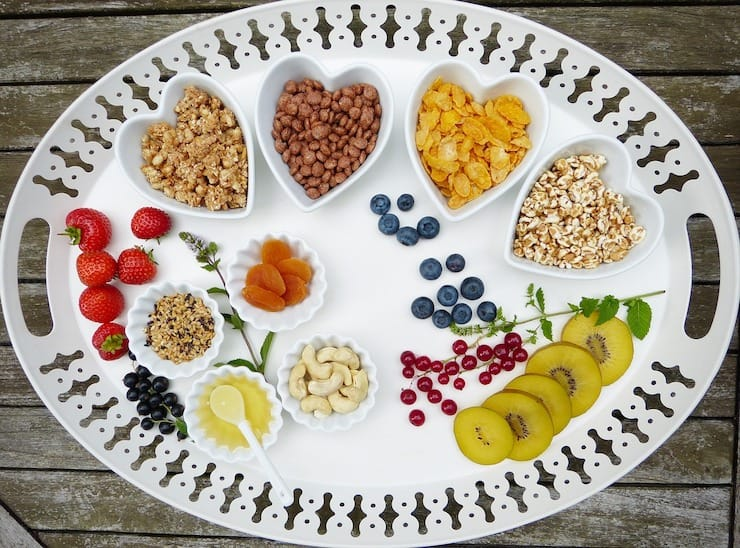 White tray with heart shaped bowls filled with cereals, fruits and nuts