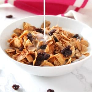 White bowl filled with aip raisin bran breakfast cereal with milk pouring on top of it on a white marble surface with raisin sprinkled on it next to a pink and white dish towel