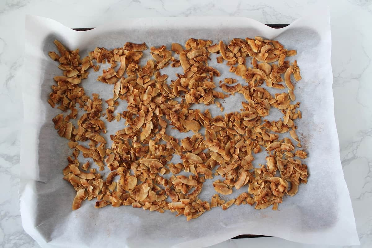Golden brown toasted coconut flakes sprinkled with cinnamon on a parchment paper lined cookie sheet