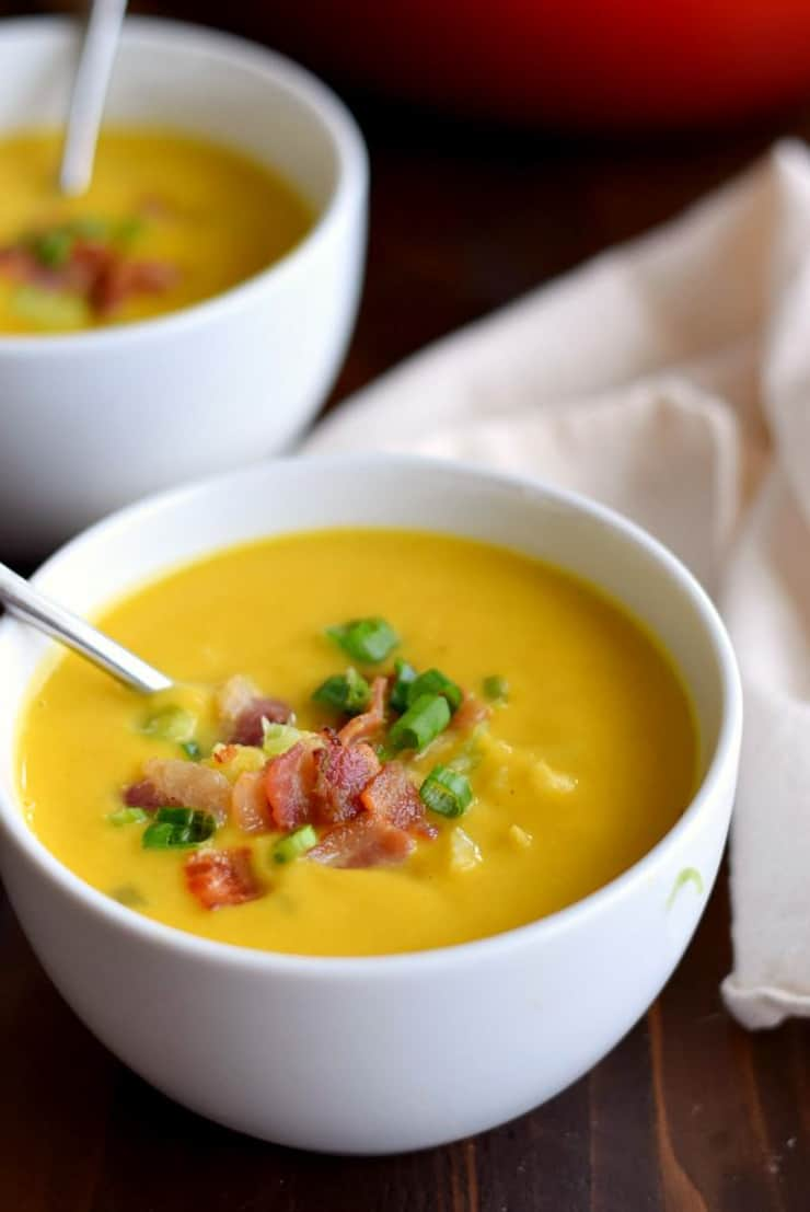 A close up of butternut squash soup in a white bowl