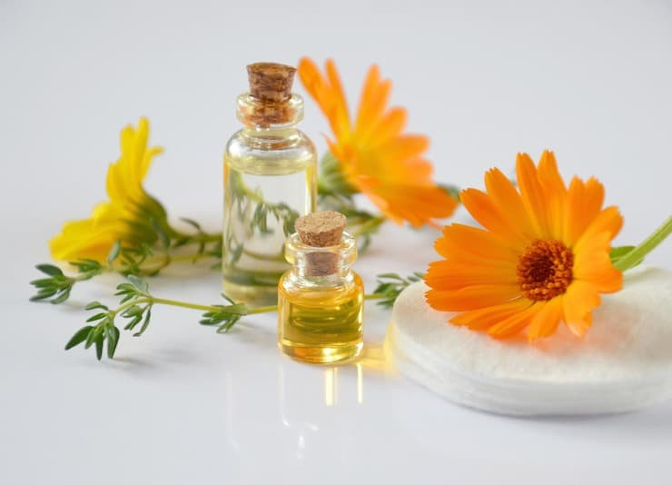 Small clear bottles of essential oils with orange and yellow flowers next to it