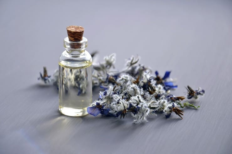 Small clear bottle of essential oil on grey surface next to purple flowers