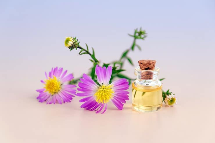 Glass bottle of essential oil next to purple flowers