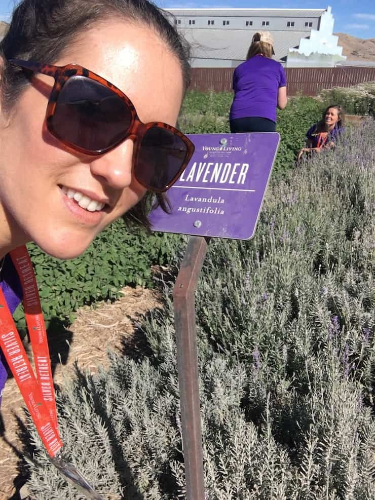 Woman smiling at camera in front of field of lavender plants with purple lavender sign