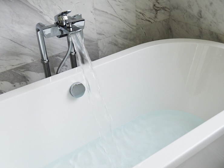 A bath tub with running taps