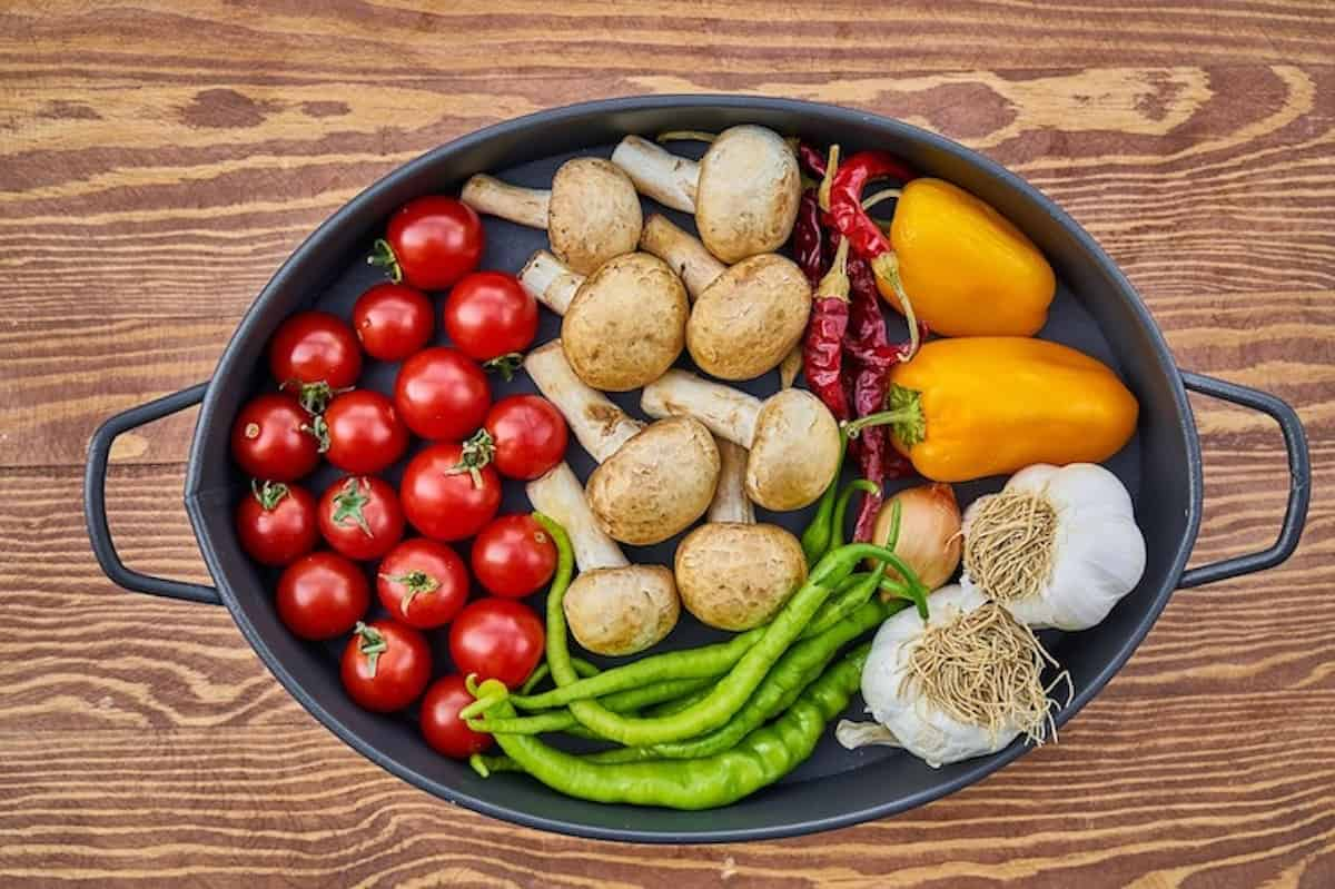 Large pot filled with raw vegetables on a wooden table