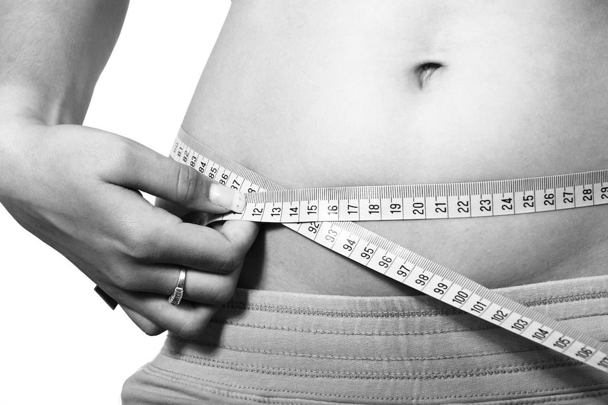 Close up on woman's abdomen with her holding a tape measure around it