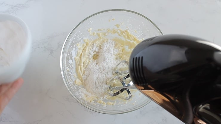 White cream filling with confectioners sweetener added on top in a clear bowl with an electric beater mixing it