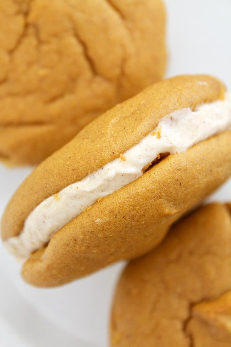 One closeup side view of a paleo pumpkin whoopie pie with two orange brown cookies and white cream in the middle