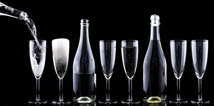 line of champaign glasses and bottles of champaign with black background
