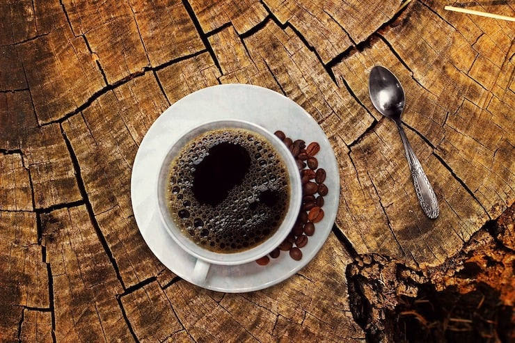 cup of black coffee on white saucer on wood stump