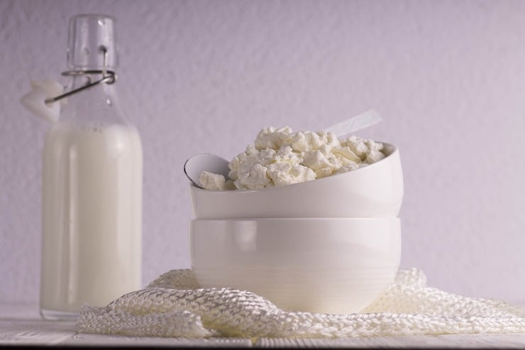 bowl of cottage cheese with glass bottle of milk in background