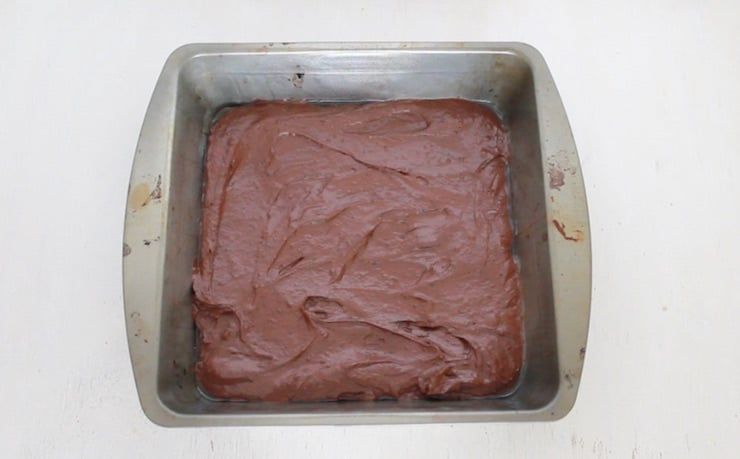 Metal pan with uncooked brownie batter in it on white table