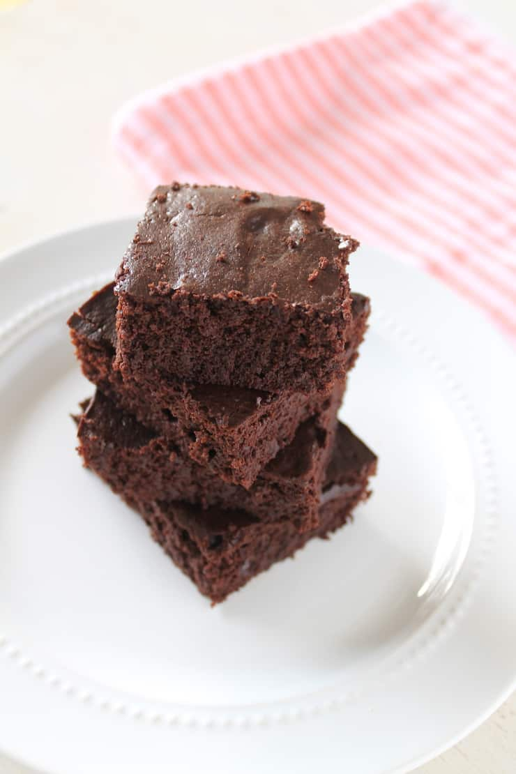 Four stacked flourless brownies on a white plate