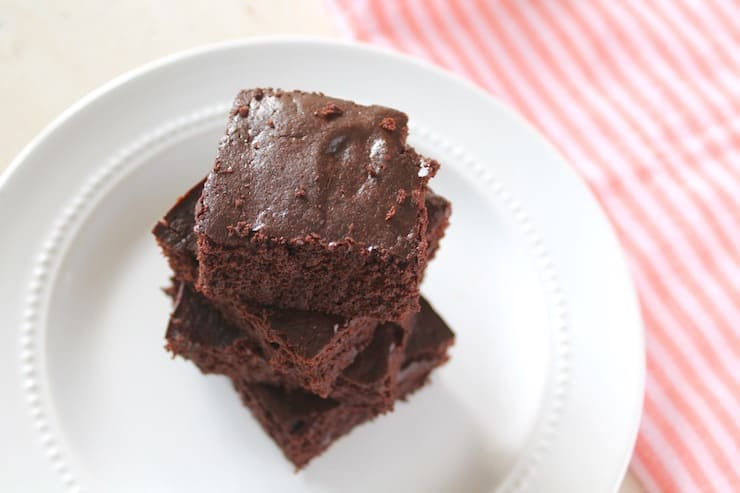Overhead view of stacked flourless brownies on a white plate next to a pink striped dish towel