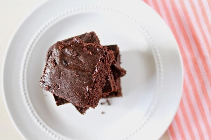 Overhead closeup of stacked flourless brownies on a white plate