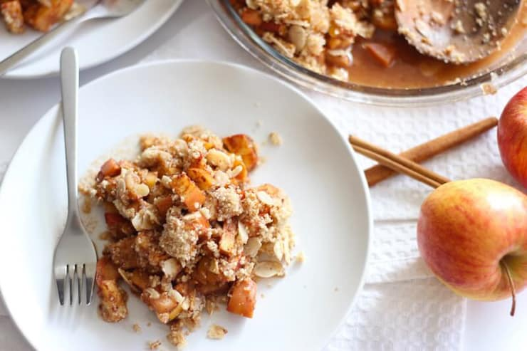 A white plate with paleo apple crisp and whole apples at the side