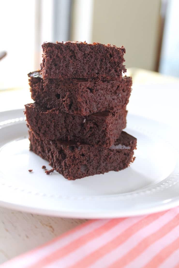 Close up of four stacked brownies on a white plate